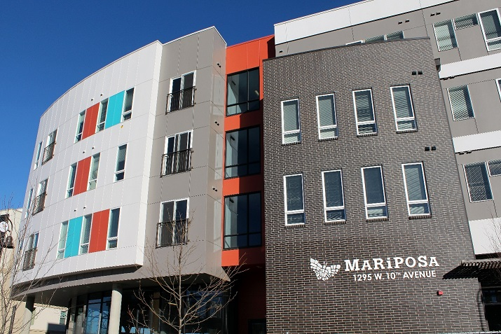 Exterior image of a multi-story, mixed-use building that incorporates several different materials and colors into the façade and bears the Mariposa name and butterfly logo.