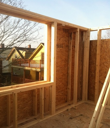 Photograph taken from an upper floor of one of the townhouses during construction. The photo shows the wood framing of the double stud walls and an open sky above. There is a gap in the framing for a window on the left side of the photograph with a view of two houses in the background.