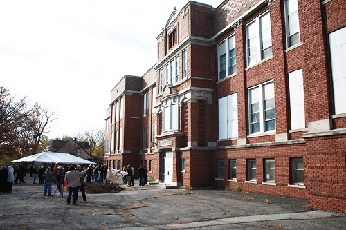 Photograph of the front façade of a three-story brick school building with several windows boarded up.