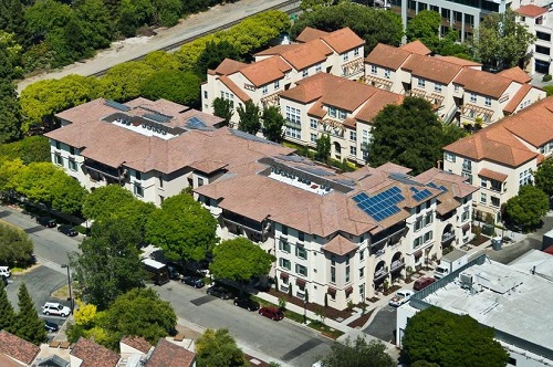 Low-angle aerial photograph of the four-story, c-shaped Franklin Street Family Apartments development. The building features a Mediterranean design and the roof includes solar photovoltaic panels. To the rear of the development are apartment buildings with a similar design.