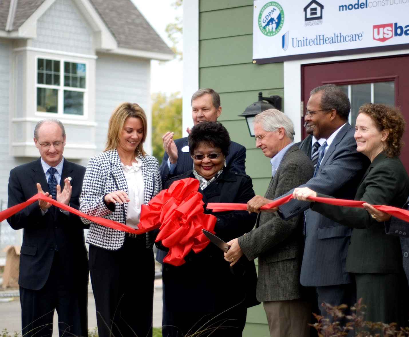Photograph of eight people cutting a ribbon to officially open the Germantown Village development.