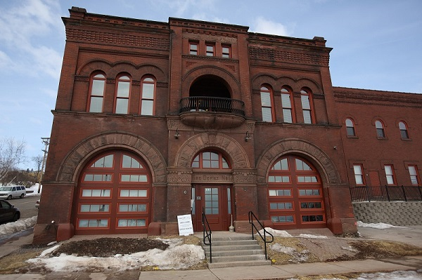 View from street level of Firehouse No. 1, and a portion of its annex behind and to the right of the firehouse. Romanesque features such as intricate brick-work, stone detailing, and arched windows distinguish the National Register buildings.