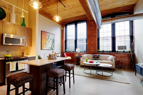 Photograph of the kitchen and living area in a Winchester Lofts unit with a very high ceiling and four large windows.