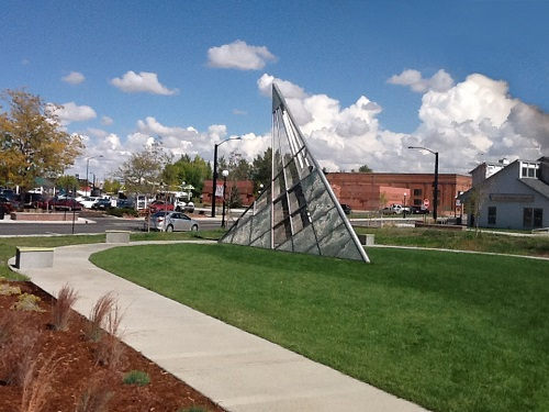 Photograph of a metal and glass sundial art piece approximately 10 feet tall standing in a lawn and encircled by a sidewalk. A large brick building and a smaller structure with siding, as well as a street with parked cars, are in the background.