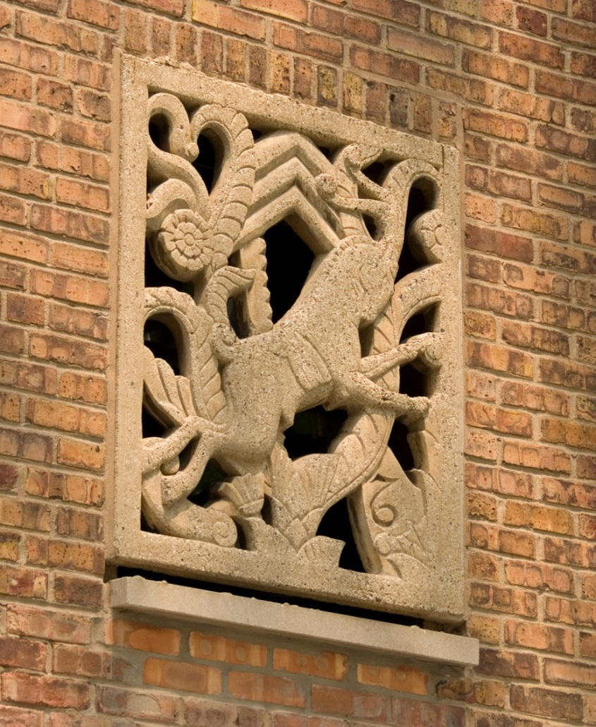 Photograph of a restored bas relief set in a wall of repointed brick. A running antelope is the central feature of the stylized sculpture, with geometric and natural shapes also set within the rectangular frame.