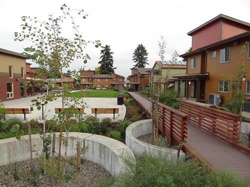 Photograph of several two-story buildings enclosing a landscaped courtyard that includes a lawn area, trees, a wooden walkway, and a paved area with several benches.