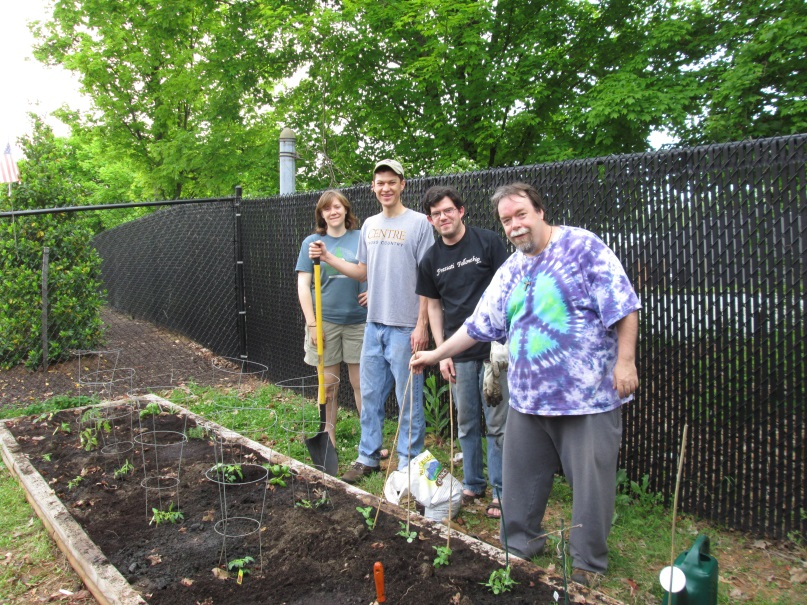 Photograph of three men and one woman standing beside a garden bed that they have been tending. About a dozen plants are sprouting in the bed that is edged by wooden four-by-four boards. Behind the gardeners is a slatted chain-link fence.