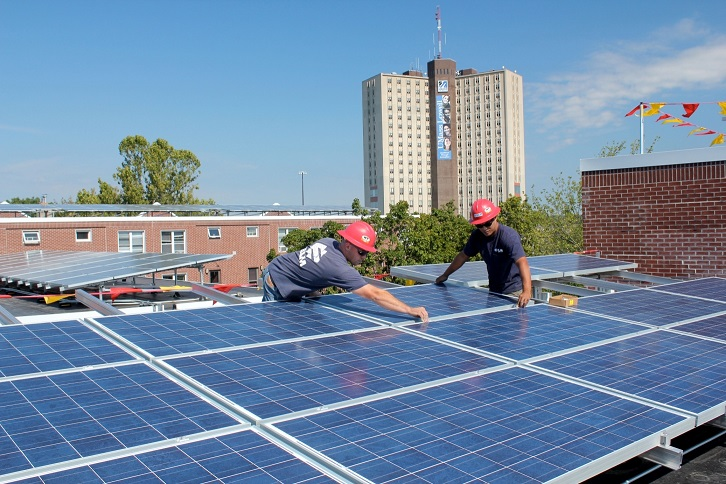 Photograph of two workers affixing a solar panel to an array of panels on the flat roof of a midrise building. The tops of a midrise and a high rise building are in the background.