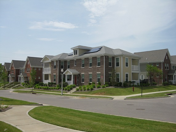 Photograph of a two-story residential building with solar panels on the pitched roof.