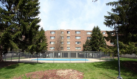 Image displaying the rear side of a multistory, brick residential building (2000 Illinois), as well as a covered swimming pool, enclosed by a fence and surrounded by grass and large trees.