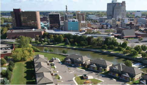 Photograph taken of downtown Flint, Michigan. Six low-lying buildings in the foreground lie adjacent to a river that runs through the center of the photograph. A variety of low- and mid-rise buildings can be seen in the background of the photograph.