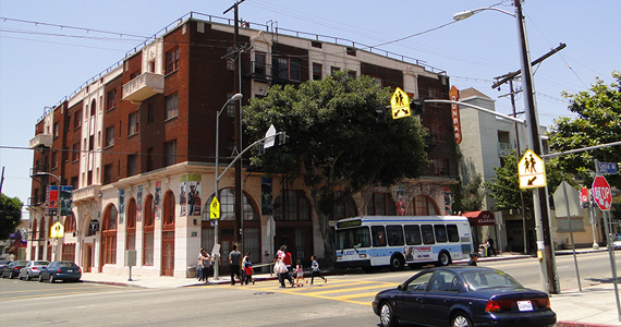 Photograph taken at street level of the Dunbar Hotel in Los Angeles. The building has a brick façade, large entry doors, and multiple windows. Trees in the foreground add aesthetic value to the building.