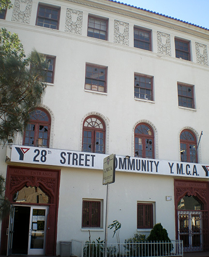 Photograph of the front façade of the 28th Street YMCA in Los Angeles. The building is shown to have large windows and landscaping along the front wall.