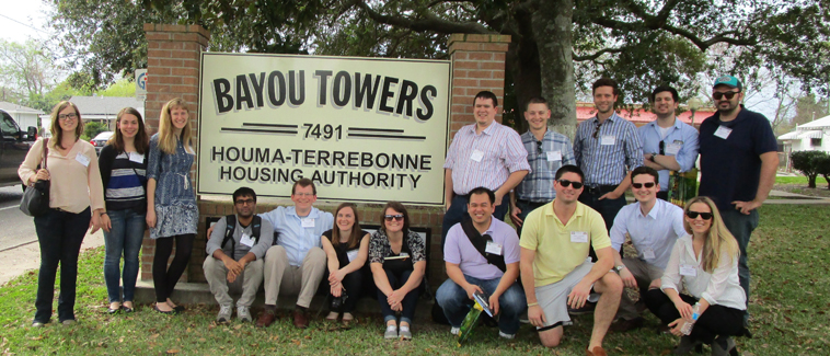 Photograph of 16 students surrounding around a large sign marking the Bayou Towers property.