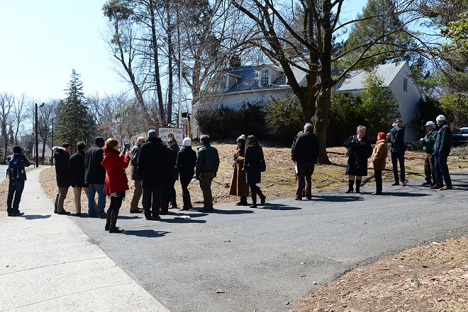Image of over 20 individuals observing and photographing the Peter DeBaun House, partially obscured by shrubs and trees, and surrounding property.