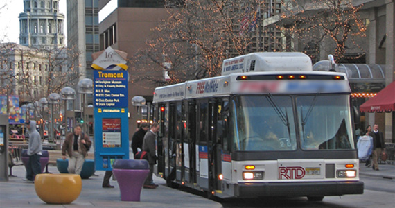 Image of passengers boarding an RTD bus at a bus stop in downtown Denver, surrounded by tall buildings.