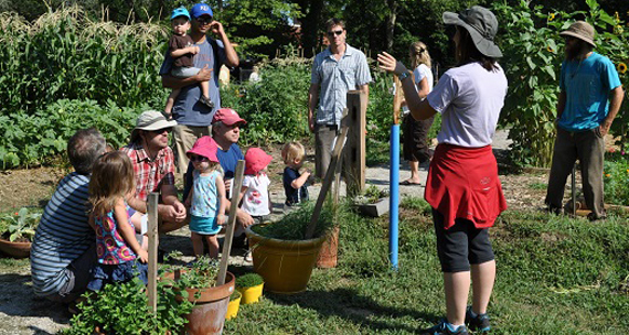 "Image of Justina Gonzalez, co-founder of a children's themed Common Ground garden, speaking to a group of parents and children about the vegetables in the garden before embarking on ""The Great Veggie Hunt."""