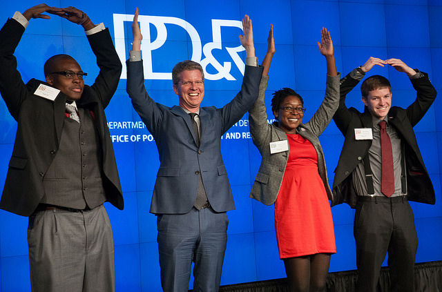 "Four individuals, including three members of the Ohio State University team and HUD Secretary Shaun Donovan (second from left), pose in front of a backdrop with a PD&R logo, using their arms to spell out the word ""Ohio."""