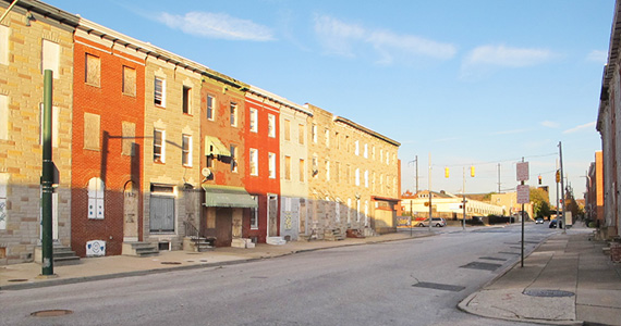 Exterior image of townhomes lining a street in East Baltimore. Boards cover the windows of several residential units.