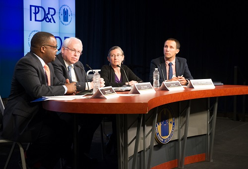 Four individuals sit at a table on stage with name cards and microphones; the PD&R logo is visible on a screen in the background.
