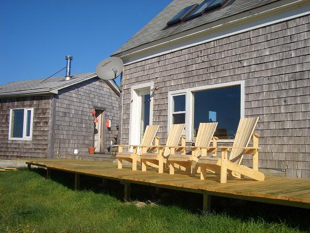 Image of a Nova Scotia home with a shared porch where a room has been removed. The main house is  in the foreground; the cottage is on the left.