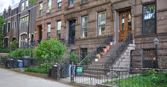 Exterior image of Brooklyn brownstone townhomes with gated entrances from the sidewalk.