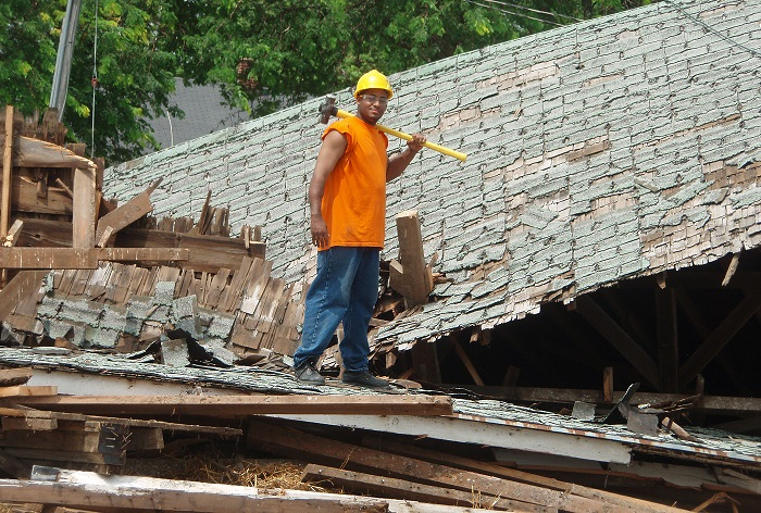 A worker deconstructing a roof.