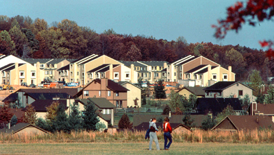 An image of two residents walking in front of a housing development.