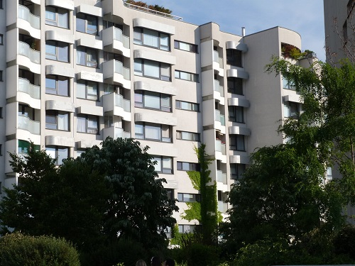 Photograph taken at street level showing a façade of one of the buildings of the Wohnpark Neue Donau housing community. The housing units are shown to have balconies and large windows. Trees in the foreground beautifully frame the view of this seven-storied building.