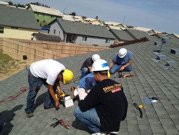 Five students in hard hats working on a roof to install a solar system.