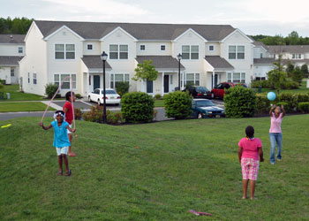 Four children play in a yard adjacent to two-story residential units within the Ethel Lawrence Homes community.