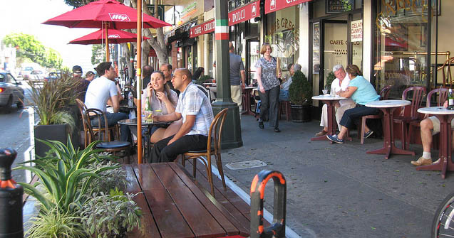 Café sidewalk scene with people, tables, and umbrellas