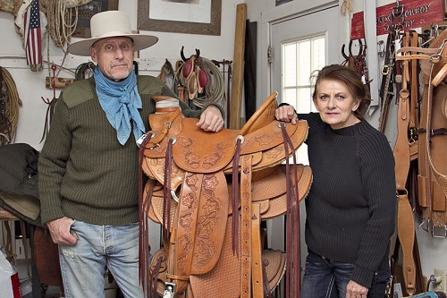 Photograph showing two individuals, a man and a woman, standing on either side of a stack of saddles on display.