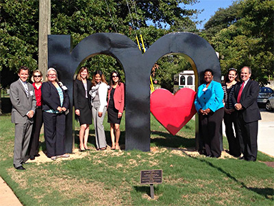 "Image of nine individuals gathering around an approximately 8 foot tall lower case letter ""m"", containing a heart in the second curve."