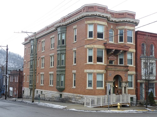 Photograph Of A Three Story Brick Building At The Intersection Of Two  Streets. A