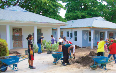 Homebuyers and volunteers provide sweat equity and labor to build Habitat for Humanity homes in Miami, Florida.