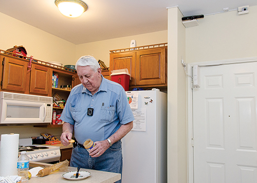 An 85-year-old man making a snack in his kitchen where an electronic sensor on the wall can call for help if he experiences a fall.
