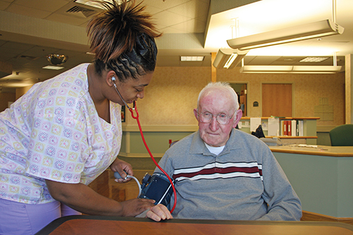 A nurse taking a blood pressure reading for an elderly man living in a nursing home.