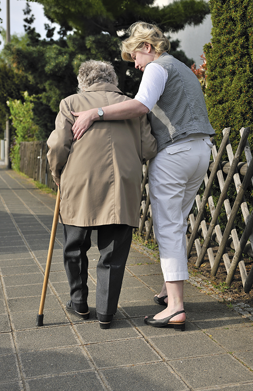 An older woman walking down a sidewalk, aided by the use of a cane and a walking companion.