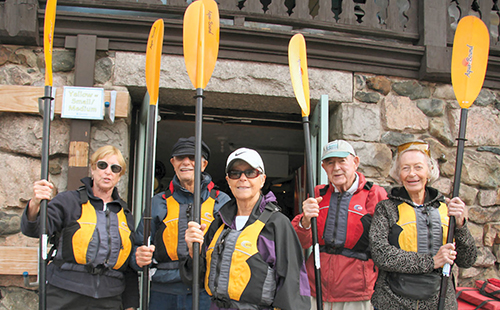 A group of five men and women who are members of Newton at Home ready to go kayaking, prepared with water resistant clothing, life vests, and paddles.