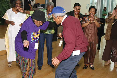 "An elderly dancing couple, surrounded by fellow East Point NORC members who are applauding and enjoying their ""moves."""