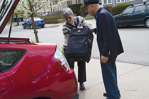 A Newton at Home volunteer driver loading an elderly man's suitcase in the trunk of her car in preparation for providing him with a ride.