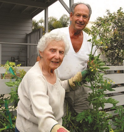 A Concierge Club member receives assistance with her gardening from a volunteer.