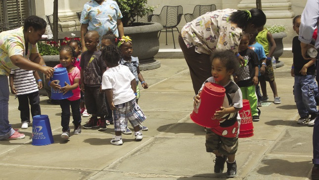 A group of preschool children with adults helping them with an organized, coordinated play activity.