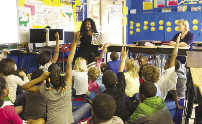 A classroom showing students excitedly interacting with a teacher.