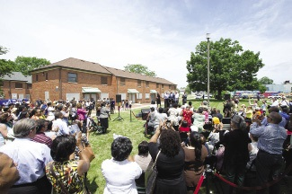 A large group of community members gathered on a lawn to commemorate the opening of a nearby mixed-income housing development.
