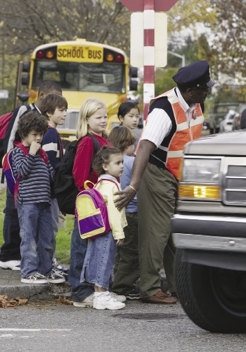 A group of young school children being helped to cross a busy street by a school crossing guard.