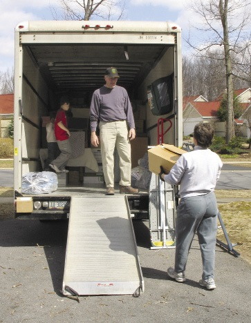 A family loading boxes onto a moving truck.