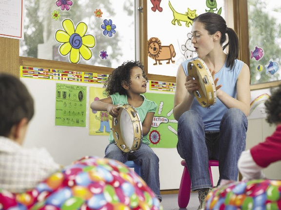 A young girl and her teacher playing musical instruments together.