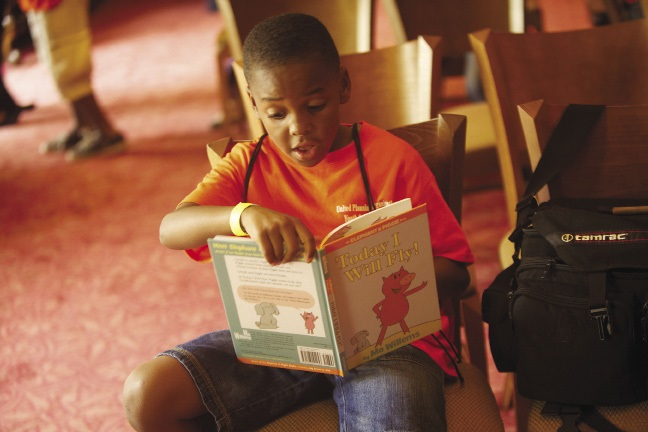 A young boy reading aloud from a book.